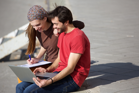 Portrait of a young male and female students sitting outdoors looking at laptop photo