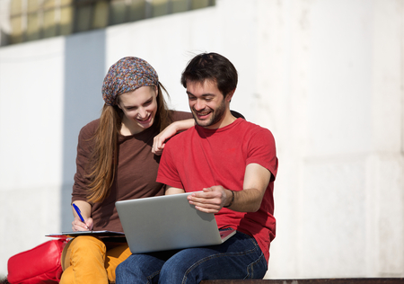 Portrait of two university students studying with laptop outdoors photo