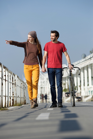 Portrait of a happy young couple walking outdoors pointing photo