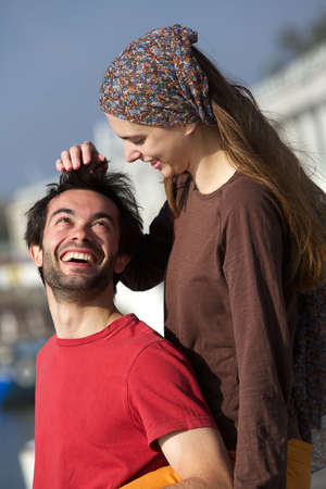 Close up portrait of happy young playful couple smiling together outdoors photo