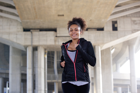 woman alone: Close up portrait of a smiling young woman jogging in urban environment Stock Photo