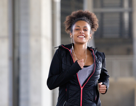 black woman: Portrait of a smiling young woman running outdoors with earphones