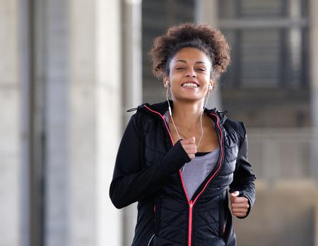 Portret van een lachende jonge vrouw loopt buiten met oortelefoons