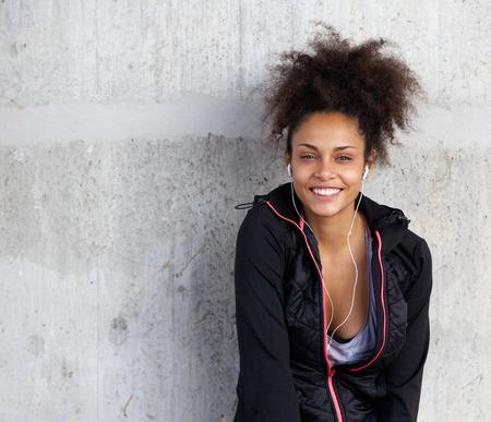 modelos negras: Cerca de retrato de una joven alegre escuchando m�sica con auriculares