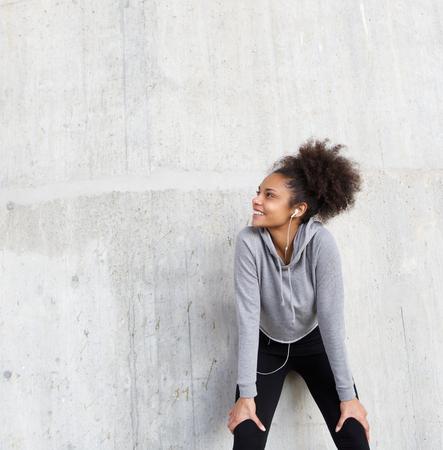 persone nere: Primo piano ritratto di un attraente giovane donna sorridente di fitness con gli auricolari