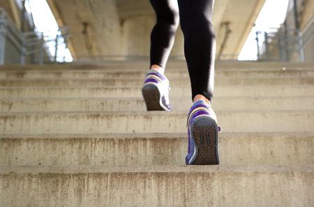 背面ビュー スポーツ女性階段を実行しています。