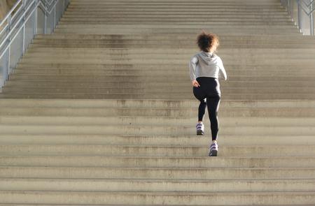 背面ビュー若い女性アスリート階段を実行