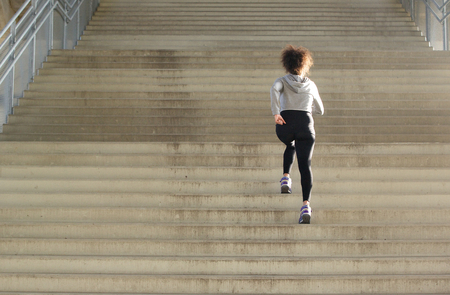 Rear view young female athlete running up stairs Foto de archivo