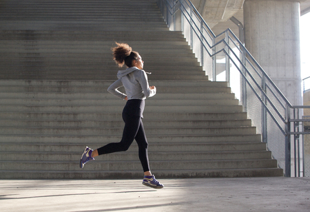 concrete stairs: Side view portrait of a healthy young woman running in urban environment Stock Photo