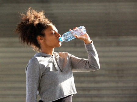 Close up portrait of a young african american sports woman drinking from water bottle
