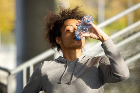 若いスポーツ女性がボトルから水を飲むの肖像画を間近します。