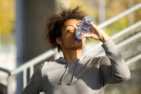 water park: Close up portrait of a young sports woman drinking water from bottle Stock Photo