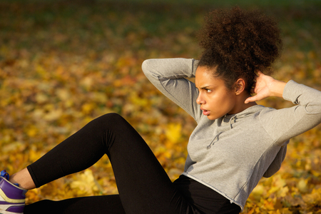 ejercicio: Retrato de una sentada mujer joven ejercer ups aire libre