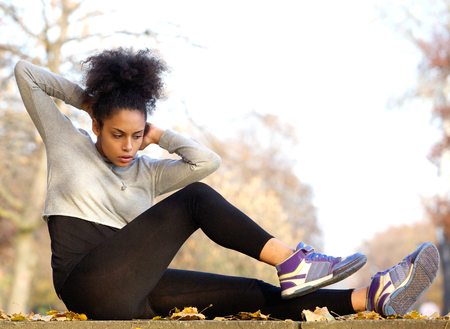 Young african american woman exercising sit ups outdoors Stock Photo