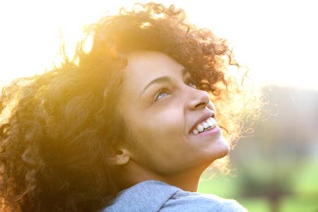 Close-up portret van een mooie jonge Afro-Amerikaanse vrouw die lacht en opzoeken