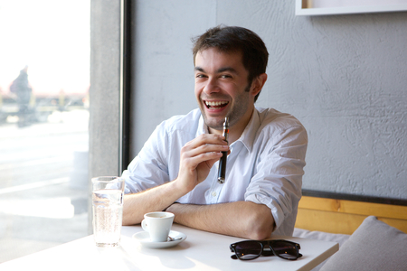 Close up portrait of a smiling young man sitting indoors with electric cigarette in hand photo