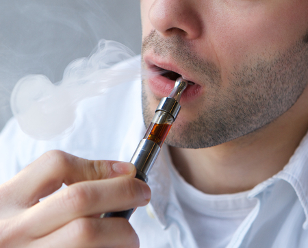 Close up part face of young man exhaling smoke from electric cigarette