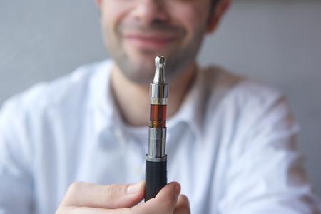 Part face close up man holding electric cigarette photo