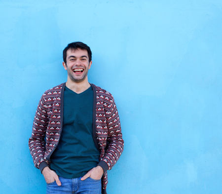Portrait of a young man laughing against blue background photo