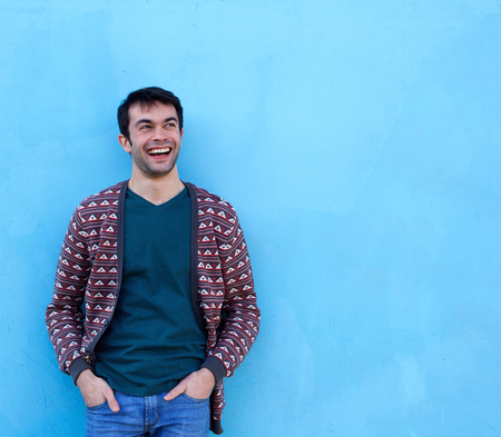 Portrait of a confident young man smiling against blue background Imagens