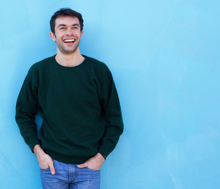 attractive male: Portrait of a charming young man smiling against blue background