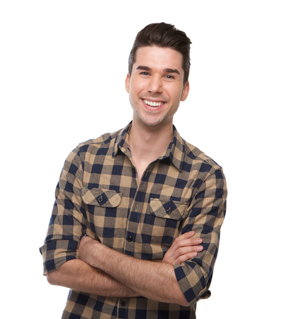 Portrait of a smiling young man posing with arms crossed on isolated white background photo