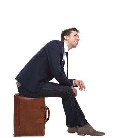 Portrait of a cheerful business man sitting on suitcase on isolated white background photo