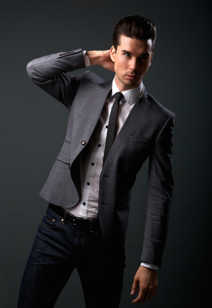 Portrait of an attractive young male fashion model in suit jacket and tie photo