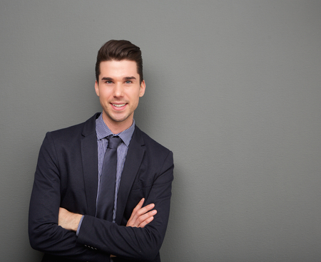 Portrait of a handsome young business man smiling with arms crossed