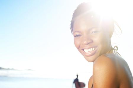 modelos posando: Close up retrato de una alegre mujer joven negro en la playa