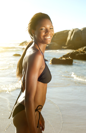 happy african woman: Side view portrait of a beautiful african american woman in bikini smiling at the beach