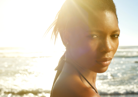 Close up portrait of a beautiful black woman posing at the beach photo
