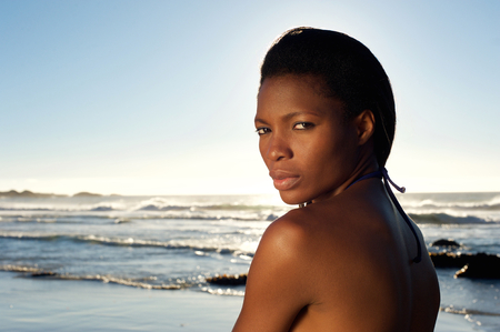 Close up portrait of a beautiful young black woman posing at the beach photo