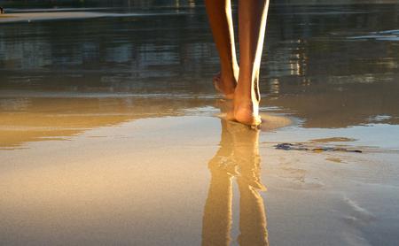 piedi nudi di bambine: Close up a basso angolo di donna afro-americana che cammina sulla spiaggia
