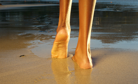 low angle views: Low angle rear view of an african american woman waling on the beach