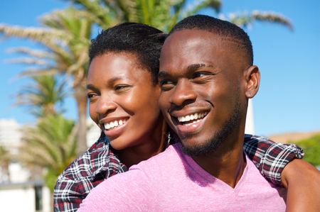 Close up portrait of a cheerful young african american couple smiling outdoors