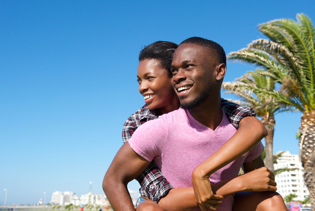 carrying girlfriend: Close up portrait of a happy man carrying girlfriend outdoors Stock Photo