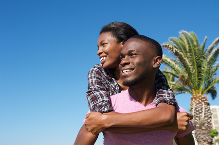 carrying girlfriend: Close up portrait of a smiling young man carrying girlfriend on back Stock Photo