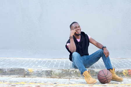 boy basketball: Portrait of a happy young african american man sitting with basketball
