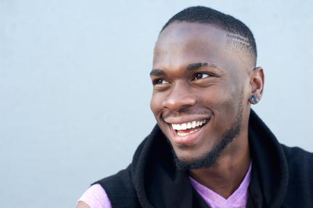 灰色の背景に対して笑っている陽気な若いアフリカ系アメリカ人の肖像画間近します。