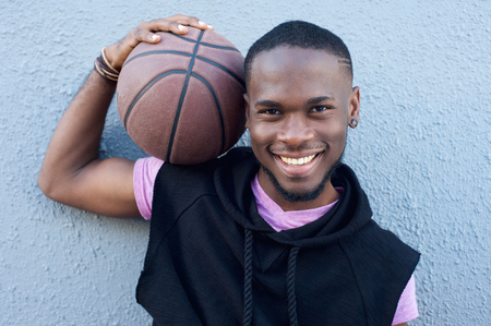 Close up portrait of a happy african american man smiling with basketball photo