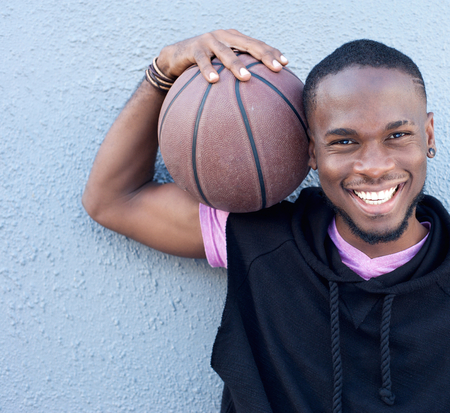 Close up portrait of a cheerful african american man holding basketball photo