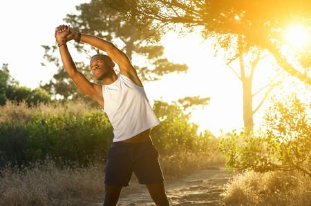 stretches: Portrait of a healthy african american man stretching muscles outdoors Stock Photo