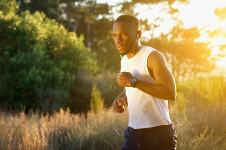 Portrait of a sporty young man running outdoors in nature photo