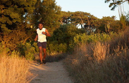 man full body: Full body portrait of a healthy young black man jogging outdoors Stock Photo