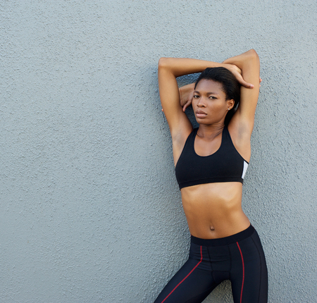 Portrait of a confident young black fitness woman posing against gray background photo