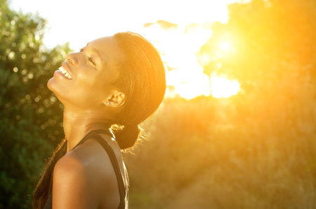 woman black background: Close up portrait of a smiling african american sports woman standing outdoors Stock Photo