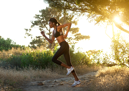 woman running: Side view full length portrait of an african american woman running outdoors Stock Photo