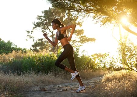 mujer cuerpo entero: Vista lateral retrato de cuerpo entero de una mujer afroamericana correr al aire libre