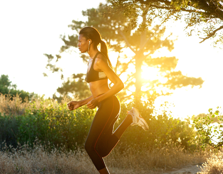Side view portrait of a fit young woman running outdoors photo